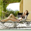 Sexy young woman relaxing on deck chair — Stock Photo #8753531