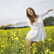Brunette woman in a yellow flowers field — Stock Photo
