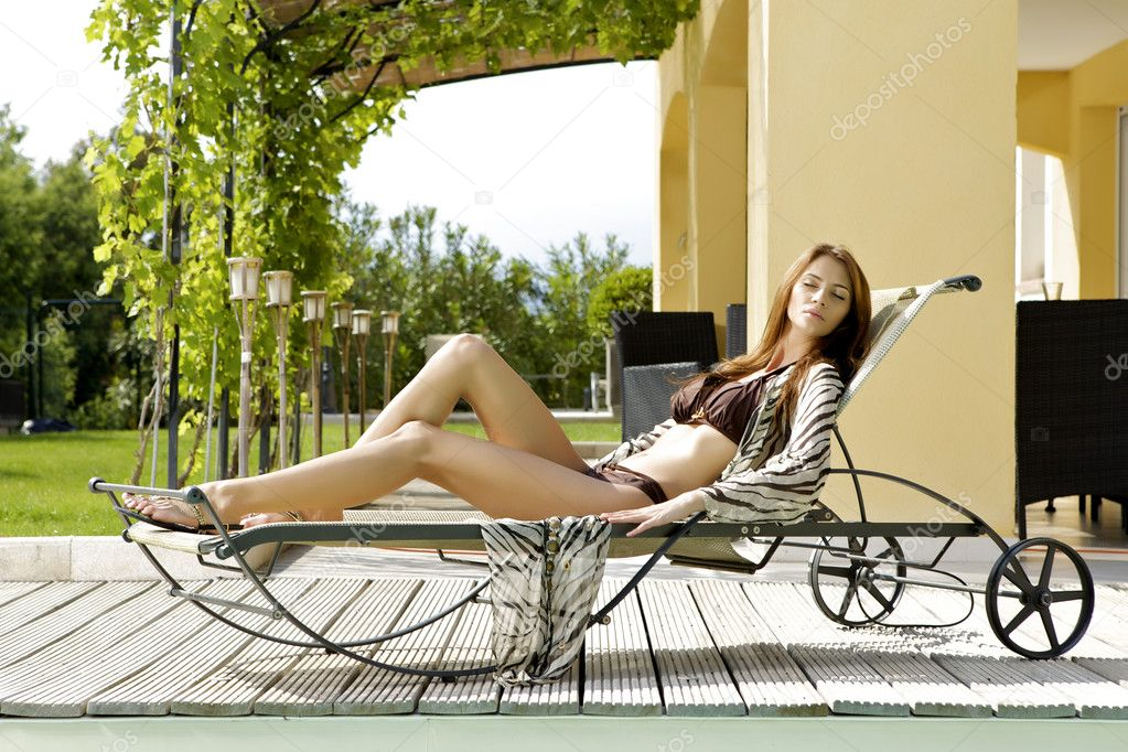Sexy and beautiful young brunette woman relaxing on deck chair — Stock Photo #8753531