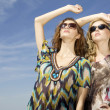 Two beautiful girl in sunglasses on background blue sky — Stock Photo #9050819