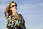 Hermosa chica con gafas de sol en el cielo azul de fondo — Foto de Stock