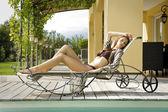 Attractive brunette in a bikini in the garden — Stock Photo