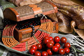 Old jewelery chest with necklaces placed on scarves — Stock Photo