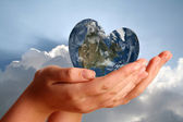 Heart shaped world in young womans hands — Stock Photo