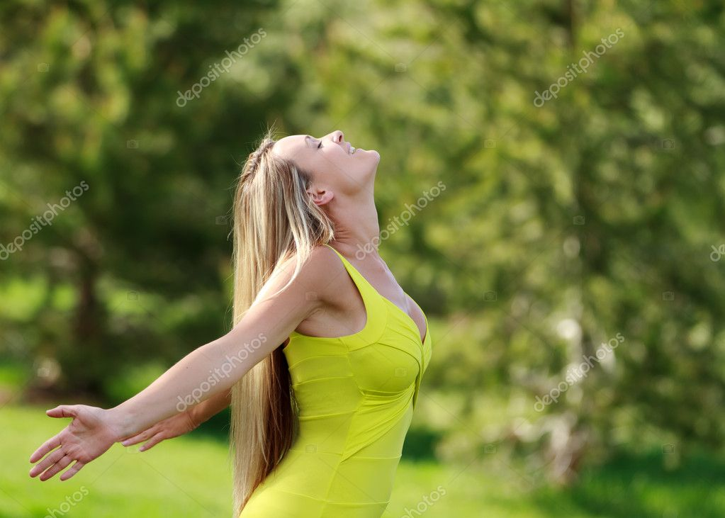 Young attractive woman at the park with face towards the sun  Stock Photo #10395545