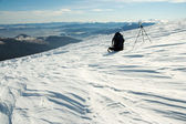 Knapsack and tripod in winter mountains — Stock Photo