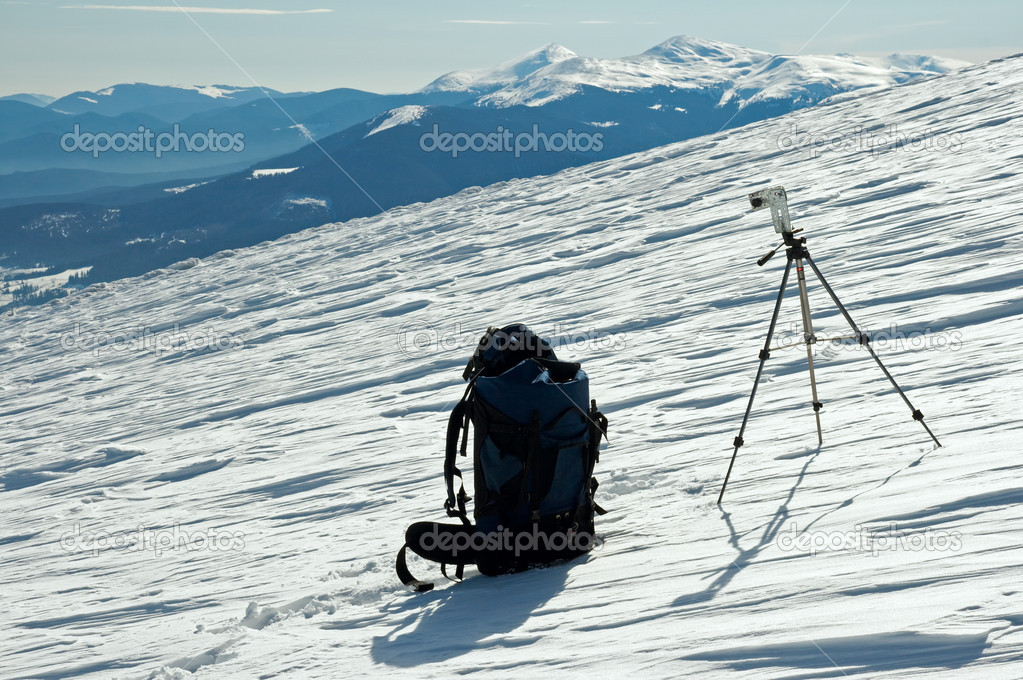 Winter mountain landscape with tourist knapsack and photographic tripod (Ukraine, Carpathian Mt's, Goverla and Petros Mountains behind) — Stock Photo #7995318