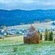 First winter snow and autumn mountain village - Stock Photo