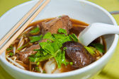 Asian cuisine, rice noodles with duck leg in white bowl — Stock Photo