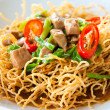Chinese style deep fried yellow noodles with pork, chili, vegetables and so — Stock Photo