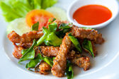 Deep fried pork with leech lime leaf and chili sauce — Stock Photo