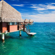 Over water bungalow with steps into clear ocean - Stock Photo