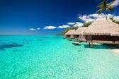 Casas de campo na praia tropical com passos na água — Foto Stock