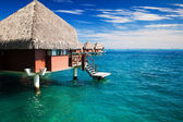 Over water bungalow with steps into clear ocean — Stock Photo