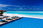 Deck and infinity pool over tropical lagoon — Stockfoto
