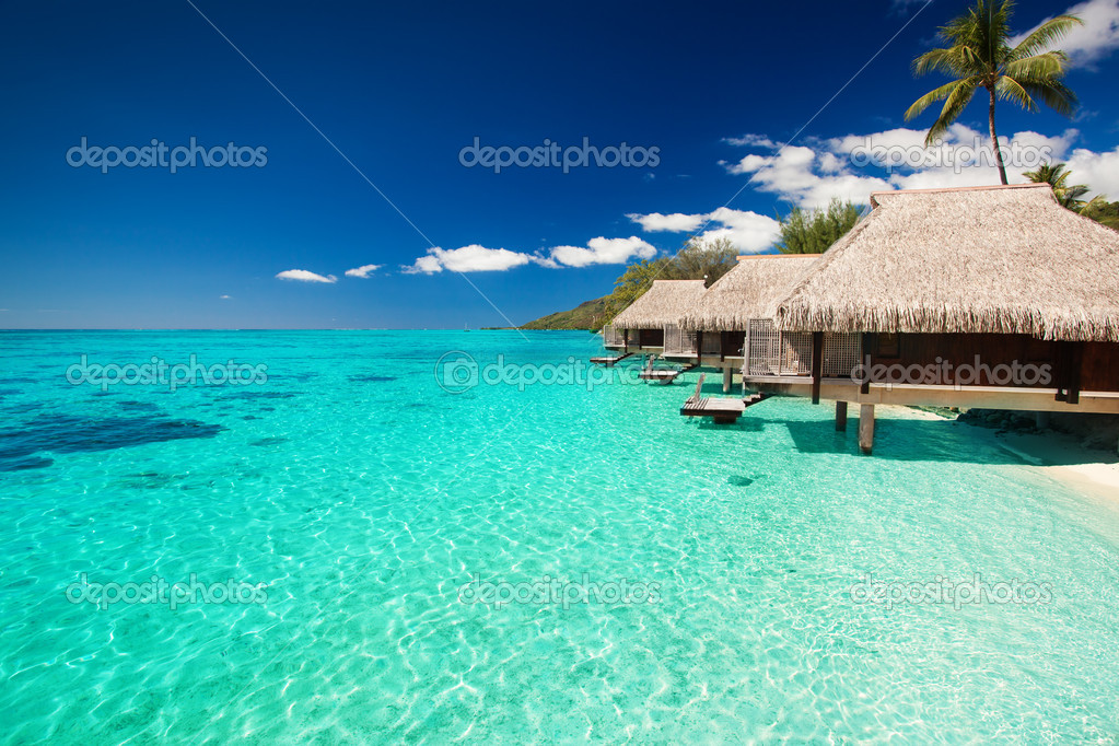 Villas on the green tropical beach with steps into water — Stock Photo #10350127