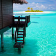 Over water bungalow with steps into blue lagoon — Stock Photo #8286628