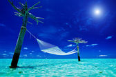 Empty over-water hammock in the middle of tropical lagoon — Stock Photo