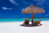 Two chairs and umbrella on stunning beach — Stock Photo