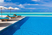 Deck chairs and infinity pool over tropical lagoon — Stok fotoğraf