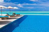 Ligstoelen en zwembad met overstroomrand over tropische lagune — Stockfoto