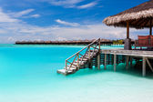 Over water bungalow with steps into blue lagoon — Stock Photo