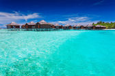 Overwater bungallows in blue lagoon — Stock Photo