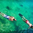 Young couple snorkeling in clean water over coral - Stock Photo