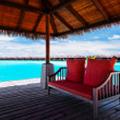 Sofa with red pillows on jetty in tropical lagoon — Stock Photo