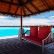 Royalty-Free Stock Photo: Sofa with red pillows on jetty in tropical lagoon