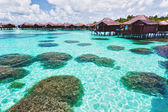 Over water bungalows and lagoon with coral — Stock Photo