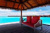 диван с красным подушки на пристани в тропической лагуны — Стоковое фото