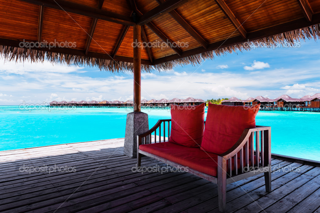 Sofa withtwo  red pillows on jetty in tropical lagoon — Stock Photo #9186426