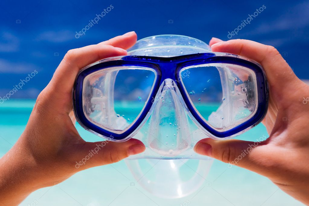 Hand holding snorkel googles against beach and sky — Stock Photo #9186510