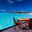 Table and chairs at beach restaurant - Stock Photo