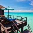 Overwater villa balcony overlooking green lagoon - Stock Photo