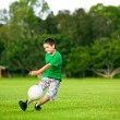 Young excited boy kicking ball in the grass — Stock Photo #9651131