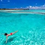 Woman in red bikini swimming in a coral lagoon — Stock Photo