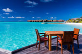 Table and chairs at beach restaurant — Stock Photo