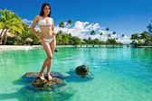 Young woman in white bikini standing on tropical beach — Stock Photo
