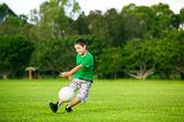 Młody chłopak podniecony, kopiąc piłkę w trawie — Zdjęcie stockowe