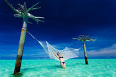 Woman leaning on over-water hammock in the middle of lagoon — Stock Photo
