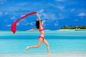 Young woman jumping on the beach with a red scarf — Stock Photo