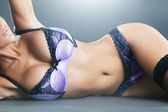 Body of woman with long hair in purple lingerie — Stok fotoğraf
