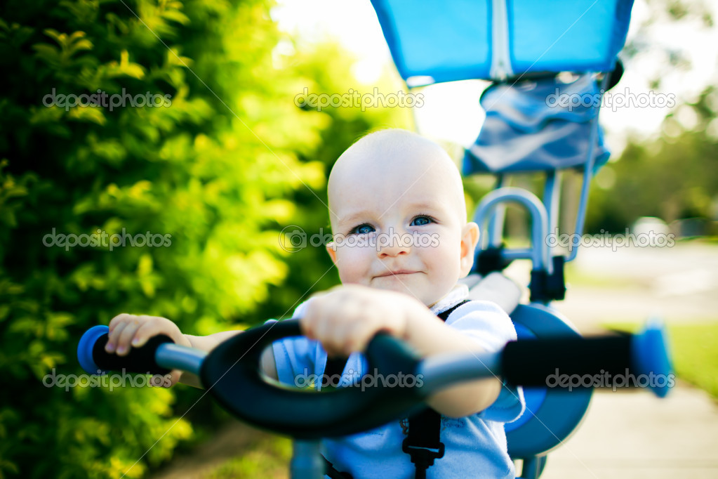 Close up of a happy child sitting on bicycle outdoors — Stock Photo #9651166