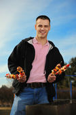 Young man has control over a shish kebab — Foto Stock