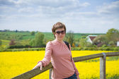 Young woman on a backgroun dof rapeseed field — Stock Photo