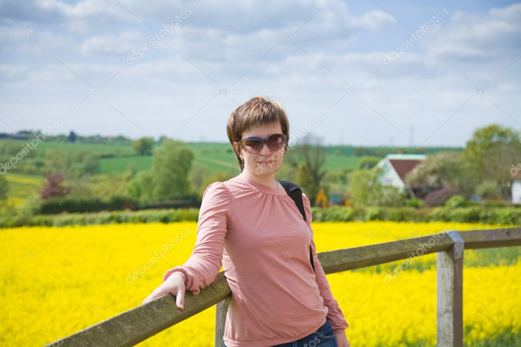 Young woman on a backgroun dof rapeseed field — Stock Photo #10230363