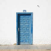 Architectural detail - faded blue door in a whitewashed wall; ol — Stock Photo