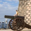Little boy in yellow t-shirt climbed a cannon - Stok fotoğraf
